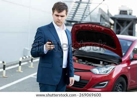 Young businessman standing at broken car and using telephone - stock photo