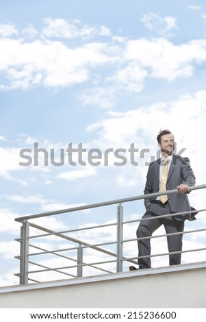 Young businessman standing at terrace railings against sky