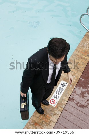 Young businessman standing at the edge of a pool.