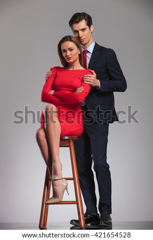 young businessman standing behind woman in red dress sitting on chair in studio