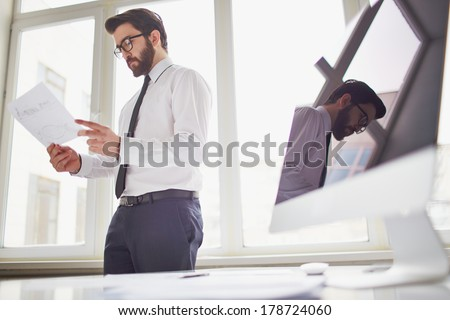 Young businessman standing by the window in office and looking at paper - stock photo