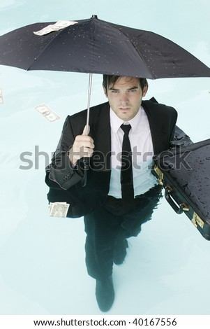 Young businessman standing in a pool with an umbrella.