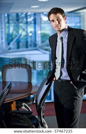 Young businessman standing in boardroom - stock photo