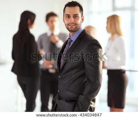 Young businessman standing in front of his associates