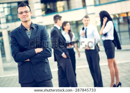 Young businessman standing in front of office building separated from the rest of the business team. With a smile looking at the camera.
