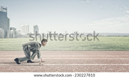 Young businessman standing in start pose ready to run