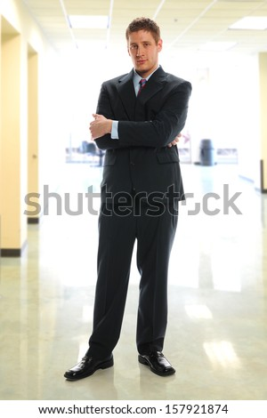 Young Businessman standing inside an office building - stock photo