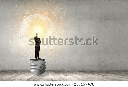 Young businessman standing inside of light bulb - stock photo