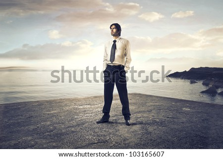 Young businessman standing on a beach