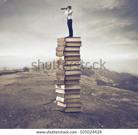 Young businessman standing on a stack of books and using a telescope - stock photo