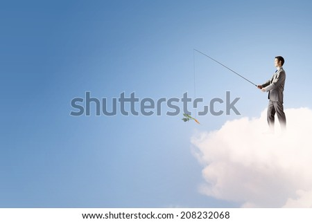 Young businessman standing on cloud high in sky and fishing - stock photo