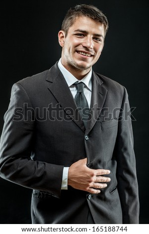 young businessman standing on dark gradient background - stock photo
