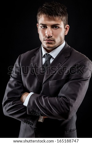 young businessman standing on dark gradient background
