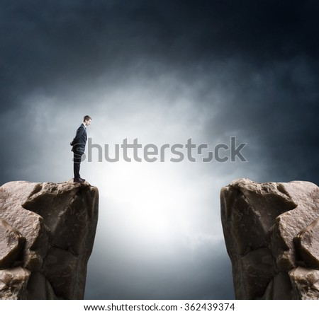 Young businessman standing on edge of rock mountain and looking  - stock photo