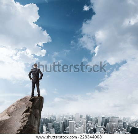 Young businessman standing on edge of rock mountain and looking at the city - stock photo