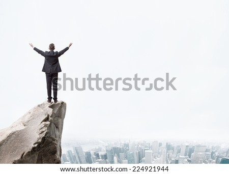 Young businessman standing on edge of rock mountain and looking at the city landscape - stock photo