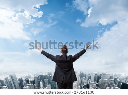 Young businessman standing on edge of rock mountain and looking at the City Manhattan downtown view - stock photo