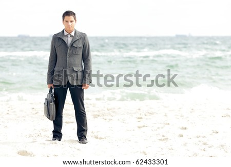 Young businessman standing on the beach - stock photo
