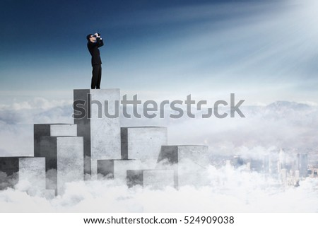 Young businessman standing on the concrete wall and looking at the sky with binoculars