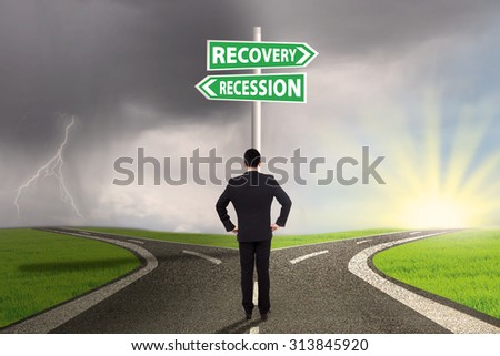 Young businessman standing on the road and looking at a signpost with two choices of recession or recovery finance - stock photo