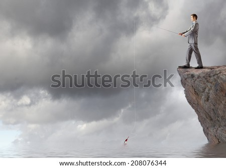 Young businessman standing on top of rock and fishing