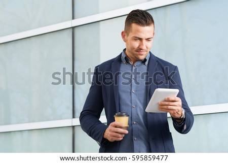 Young businessman standing outdoors on a break and using touch pad