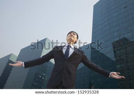 Young businessman standing outside with arms outstretched