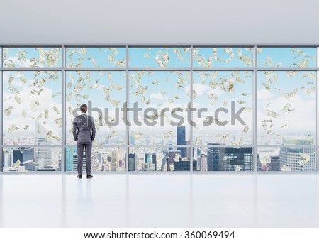 Young businessman standing with his hands in pockets looking through the window in a spacious office in a business centre. Money in the air. New York view. Concept of earning money. - stock photo