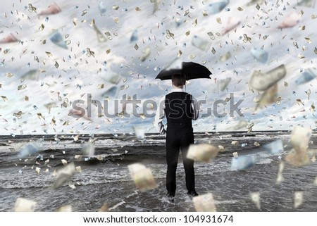 Young businessman standing with umbrella under money rain - stock photo