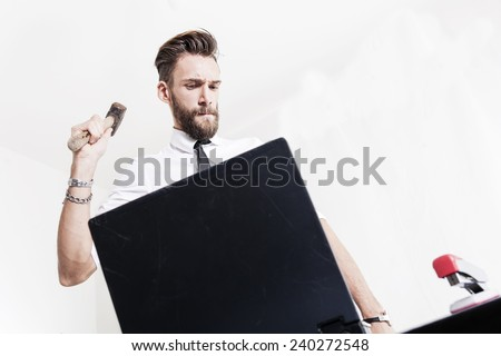 young businessman strikes hammered laptop computer - stock photo