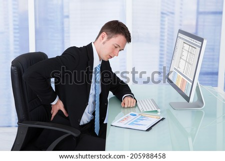 Young businessman suffering from backache at computer desk in office - stock photo