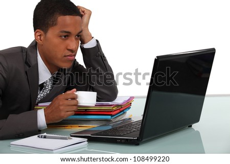 Young businessman taking a break in front of his laptop - stock photo