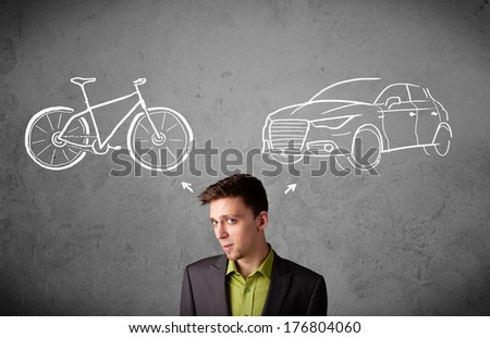 Young businessman taking a decision between bicycle and car - stock photo
