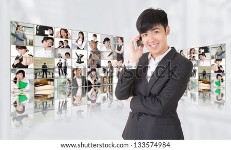 Young businessman talk on phone and stand in front of tv screen wall showing pictures of business concept by Asian business people. Concepts about business, communication, teamwork or social network.