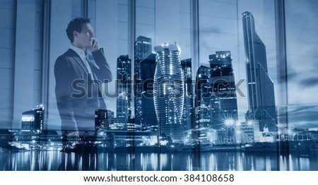 young businessman talking by phone, double exposure with modern blue city skyline - stock photo
