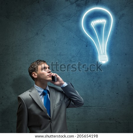 young businessman talking on cell phone and looking at the shining lamp