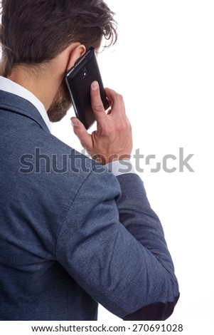 Young businessman talking on mobile isolated on white background. back view - stock photo