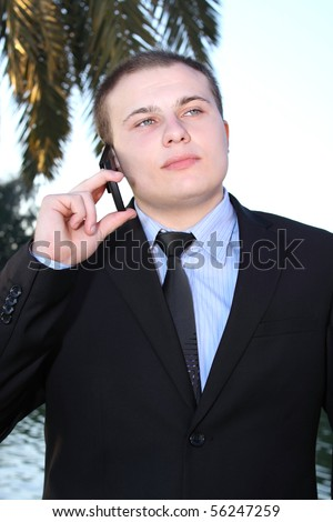 Young businessman talking on mobile phone at nature background