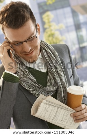 Young businessman talking on mobile phone on the way to work, holding newspaper and coffee.