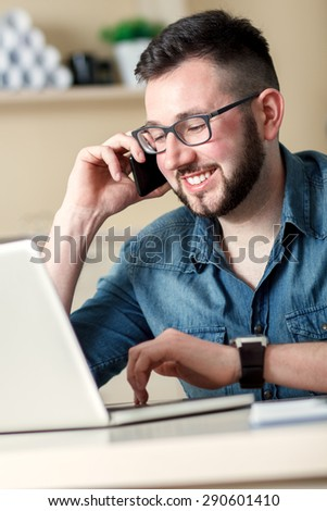 Young businessman talking on phone and working with laptop - stock photo