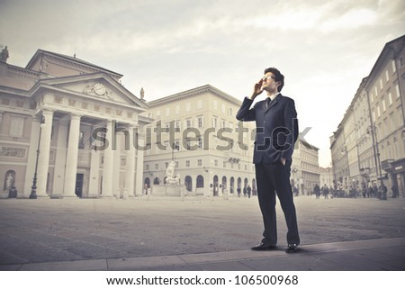 Young businessman talking on the mobile phone on a town square - stock photo