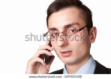 Young businessman talking on the mobile phone. On a white background. Taken close up.