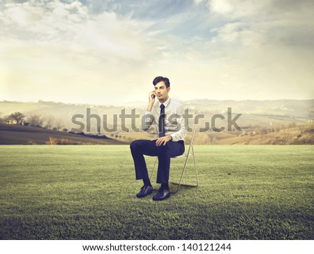 young businessman talking on the phone sitting on a chair outdoor