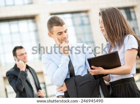 Young businessman talking to his pretty business partner in front of office building.