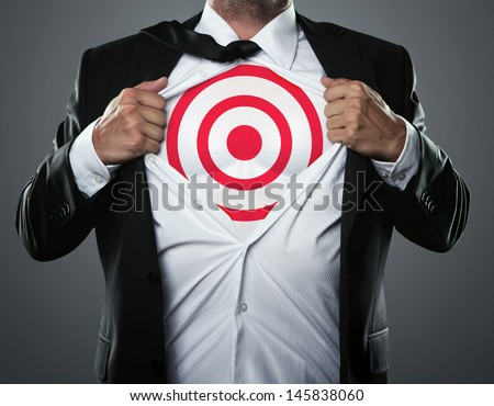 Young businessman tearing his shirt to show target symbol underneath - stock photo