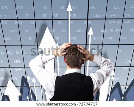 Young businessman thinking and analyzing financial graphs