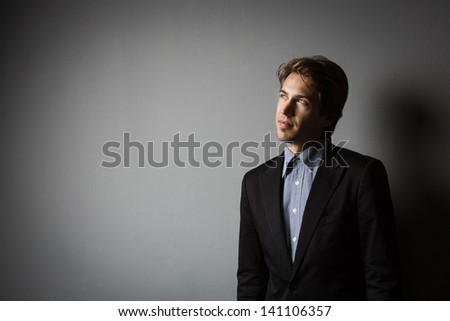 Young businessman thinking and having ideas on a gray background with copy-space on the left
