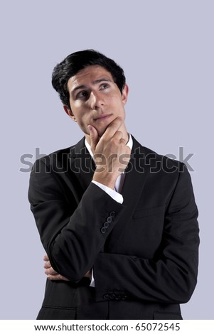 Young businessman thinking and looking up (isolated on gray) - stock photo
