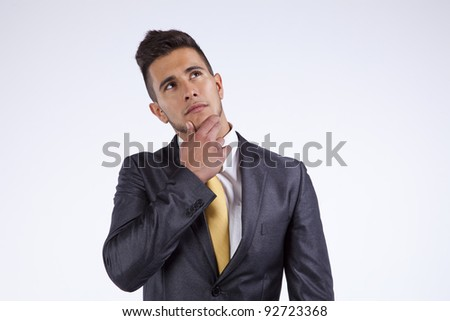 Young businessman thinking and looking up (isolated on gray - stock photo