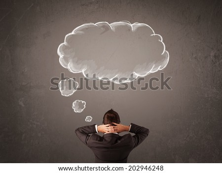Young businessman thinking in front of a wall with cloud thought above his head - stock photo